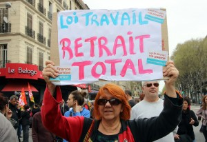 "A demonstrator holds a placard reading ""Job law, total withdrawal"", during a nationwide day of protest, in Marseille, southern France, Thursday, March 31, 2016. Student organizations and employee unions have joined to call for protests across France to reject a government reform relaxing the 35-hour workweek and other labor rules, which they consider as badly damaging hard-fought worker protections. (AP Photo/Claude Paris)"