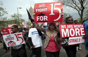 A group of workers and labor activists march down West Grand Boulevard as they demand a raise in the minimum wage for fast food workers in Detroit, Michigan May 10, 2013. Hundreds of workers in Detroit walked off the job on Friday temporarily shuttering a handful of outlets as part of a growing U.S. worker movement that is demanding higher wages for flipping burgers and operating fryers. REUTERS/Rebecca Cook (UNITED STATES - Tags: BUSINESS EMPLOYMENT POLITICS CIVIL UNREST) - RTXZI41